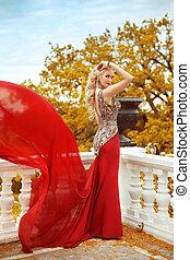 bonito, deslumbrante, excitado, mulher, em, elegante, sereia, vestido vermelho, com, soprando, ligado, a, sacada, sobre, outono, parque, vista., loura, senhora, com, casório, cabelo ondulado, estilo, em, longo, gown.