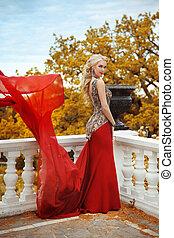 bonito, deslumbrante, mulher, modelo, em, elegante, sereia, vestido vermelho, com, soprando, ligado, a, sacada, em, outono, park., loura, senhora, com, casório, cabelo ondulado, estilo, em, longo, gown.