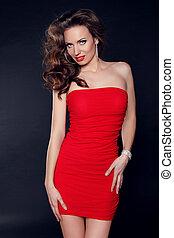 bonito, excitado, mulher, em, vestido vermelho, com, cabelo ondulado, posar, sobre, experiência escura