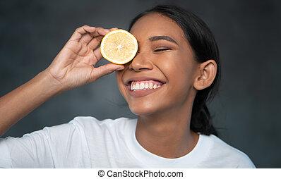 bonito, fatia, olho, mulher jovem, segurando, retrato, frente, limão, sorrindo