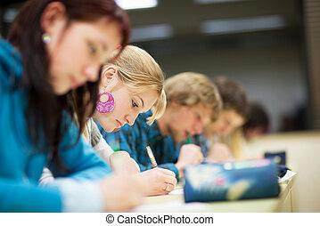 bonito, femininas, estudante universitário, sentando, um, exame, em, um, sala aula, cheio, de, estudantes, (shallow, dof;, cor, toned, image)