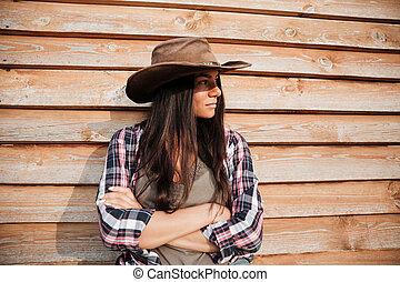 bonito, ficar, mulher, cowgirl, jovem, braços cruzaram, chapéu