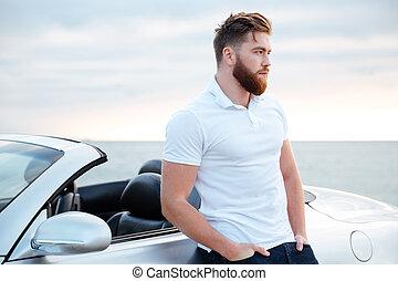 bonito, homem enfrentado, em, camisa branca, inclinar-se, car, ao ar livre