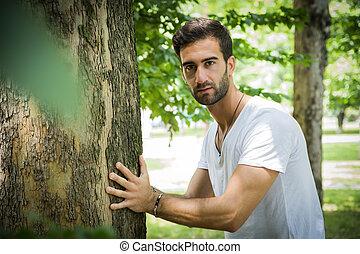 bonito, homem jovem, apoiando, árvore