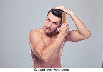 bonito, homem jovem, combing, seu, cabelo