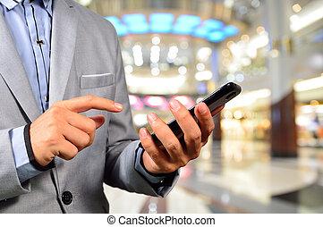 bonito, homem jovem, em, centro comercial, usando, móvel, tablet.