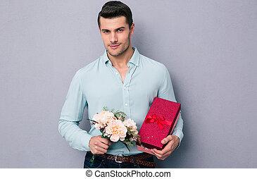 bonito, homem jovem, segurando, caixa presente, e, flores