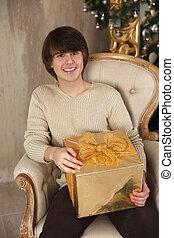 bonito, homem jovem, segurando, caixa presente, sentando, ligado, poltrona, em, bege, interior., sorrir feliz, menino, olhar, câmera.