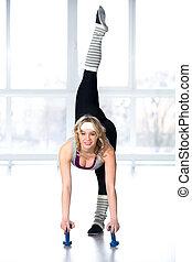 bonito, jovem, bailarino feminino, fazendo, esticar, exercícios, com, dumbbells