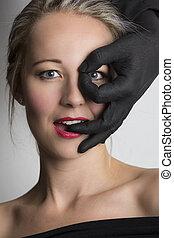 bonito, loiro, mulher olha, através, dedos, de, um, pretas, passe, dela, rosto