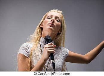 bonito, loura, mulher jovem, cantando, em, um, microfone