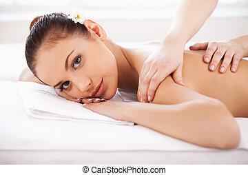 bonito, mantendo, mulher, spa., dela, jovem, costas, enquanto, terapeuta, massagem, fechado, frente, olhos, massaging, mentindo