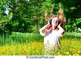 bonito, menina, em, fones, desfrutando, a, música, com, cabelo corrente, em, um, campo flores, em, natureza