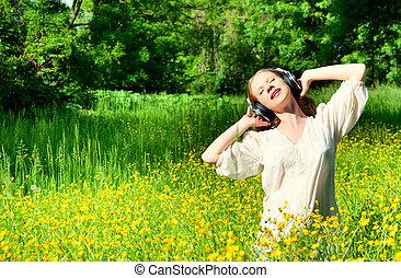 bonito, menina, em, fones, desfrutando, a, música, em, um, campo flores, em, natureza