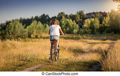 bonito, menina, em, t-shirt, ciclismo, em, prado, em, pôr do sol