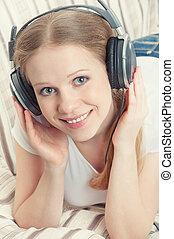 bonito, menina sorridente, desfruta, escutar música, ligado, fones, enquanto, mentindo, sofá
