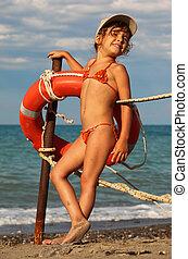 bonito, menininha, em, fato de banho, e, boné, ficar, ligado, praia., ela, clings, para, poste metal, ligado, polaco, penduradas, vermelho, bóia vida