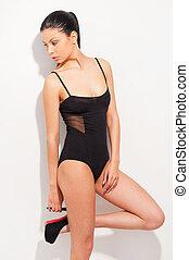 bonito, moda, model., atraente, mulher jovem, em, pretas, roupa interior, posar, e, olhando, enquanto, ficar, contra, fundo branco