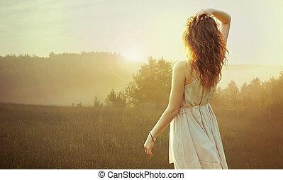 bonito, morena, mulher, assistindo pôr-do-sol