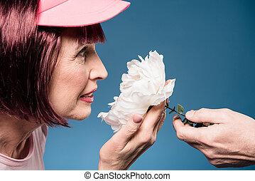 bonito, mulher idosa, segurando, e, cheirando, flor branca