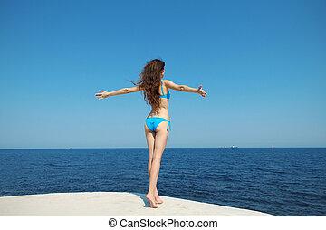 bonito, mulher jovem, aberta, dela, mãos, com, prazer, em, a, céu azul