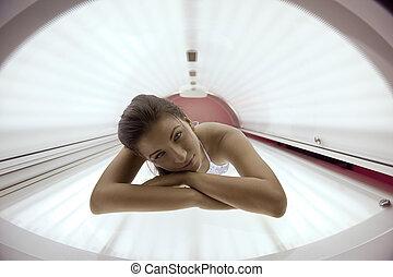 bonito, mulher jovem, bronzeando, em, solarium
