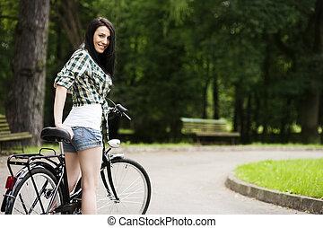 bonito, mulher jovem, com, bicicleta, parque