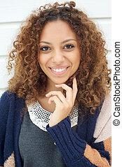 bonito, mulher jovem, com, cabelo ondulado, sorrindo, ao ar livre