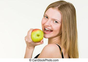 bonito, mulher jovem, com, suportes, comendo maçã