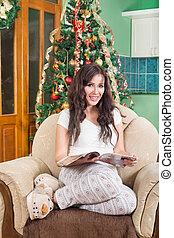 bonito, mulher jovem, compartimento leitura, sentar sofá, sorrindo