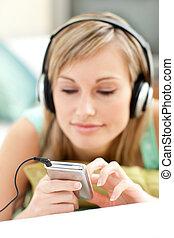 bonito, mulher jovem, escutar, música, mentindo, ligado, um, sofá