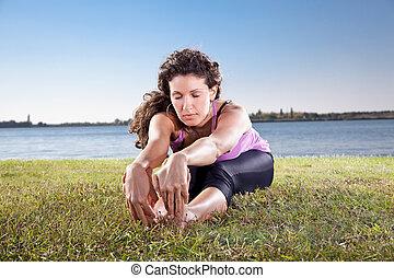bonito, mulher jovem, fazendo, esticando exercício, ligado, grama verde, perto, a, lake., ioga, concept.