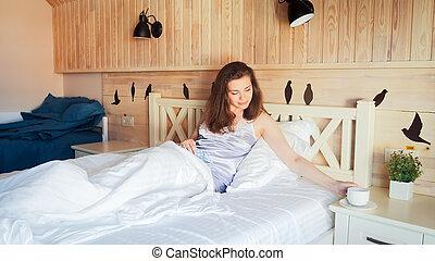 bonito, mulher jovem, mentindo cama, e, pôr, xícara chá, ligado, mesa de cabeceira
