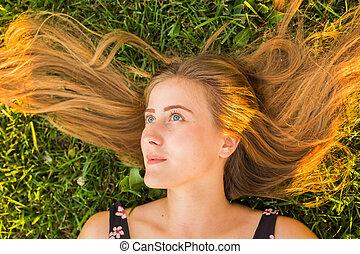 bonito, mulher jovem, mentindo, em, meadow., apreciar, natureza