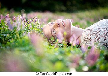 bonito, mulher jovem, mentindo, em, prado, de, flores