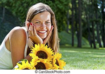 bonito, mulher jovem, mentindo, em, prado, de, flowers., apreciar, natureza