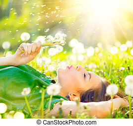 bonito, mulher jovem, mentindo, ligado, a, campo, em, grama verde, e, soprando, dandelion