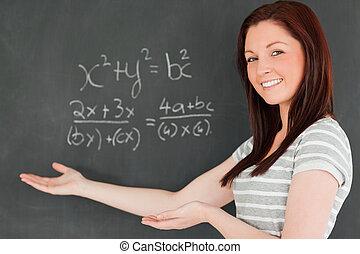 bonito, mulher jovem, mostrando, um, equação, ligado, um, quadro-negro