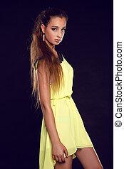 bonito, mulher jovem, posar, em, vestido amarelo, isolado, ligado, experiência preta