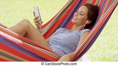 bonito, mulher jovem, relaxante, em, um, rede