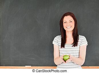 bonito, mulher jovem, segurar uma maçã, contra, um, quadro-negro