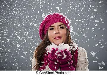 bonito, mulher jovem, soprando, neve