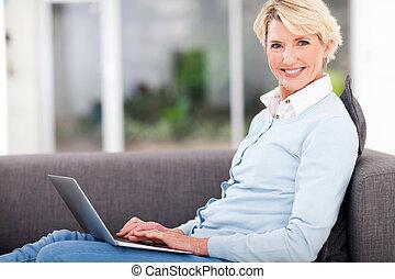 bonito, mulher sênior, casa, usando computador portátil