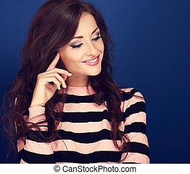bonito, mulher sorridente, olhando baixo, com, cacheados, longo, penteado, ligado, azul, experiência., closeup, retrato