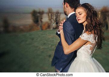 bonito, noivinhos, abraçando, campo, atrás de, closeup, emocional, pôr do sol, recém casado