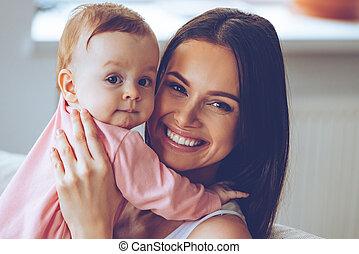 bonito, olhar, mulher, dela, sentando, daughter., mãos, jovem, sofá, alegre, enquanto, câmera, segurando, sorrizo, bebê, lar, menina, mãe