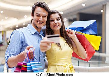 bonito, par, mostrando, cartão crédito, em, a, centro comercial