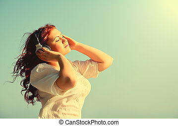 bonito, ruivo, menina, com, cabelo longo, desfruta, música, com, fones, em, a, céu, com, seu, olhos fecharam