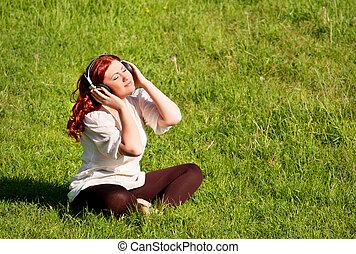 bonito, ruivo, mulher jovem, escutar música, com, fones, ligado, natureza, ao ar livre, ligado, capim, gramado