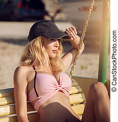 bonito, senta-se, boné, jovem, balanço banco, menina, swimsuit, praia, arenoso